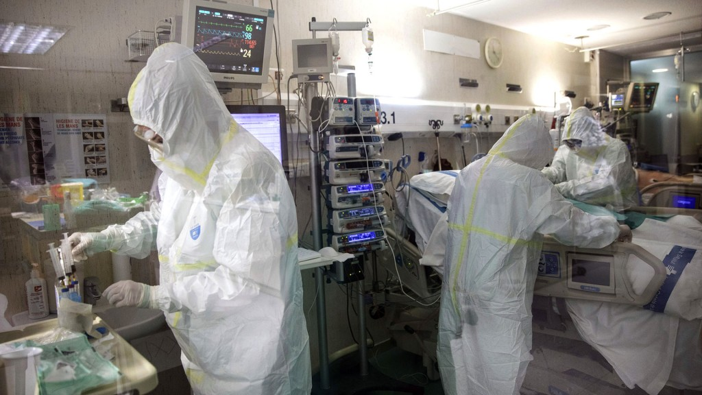 In this photo taken on Friday, March 27, 2020, healthcare workers assist a patience at one of the intensive care units (ICU) at German Trias i Pujol hospital in Badalona, in the Barcelona province, Spain. The new coronavirus causes mild or moderate symptoms for most people, but for some, especially older adults and people with existing health problems, it can cause more severe illness or death. (AP Photo/Anna Surinyach)